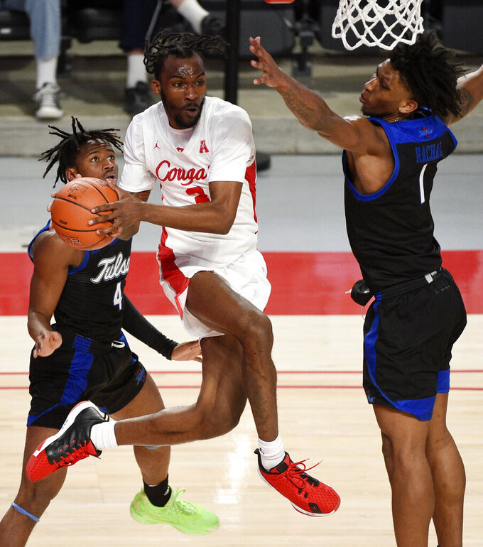 Houston guard DeJon Jarreau, middle, looks to pass as Tulsa guard Brandon Rachal, right, defends during the second half of an NCAA college basketball game Wednesday, Jan. 20, 2021, in Houston. (AP Photo/Eric Christian Smith)