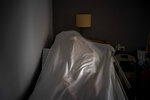 The body of an elderly person who died of COVID-19 is covered with a sheet on a bed in a nursing home in Barcelona, Spain, Friday, Nov. 13, 2020. Like doctors and nurses, mortuary workers are part of a group of essential workers who see and touch the daily march of death amid the worst public health crisis in over a century. (AP Photo/Emilio Morenatti)