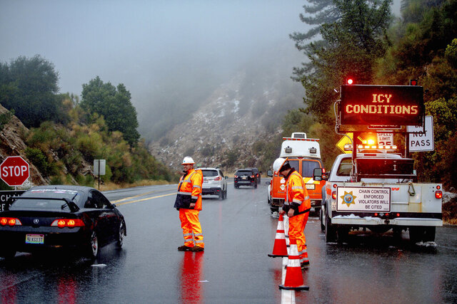 The first snowfall of the season hits San Bernardino Mountains as Caltrans set chain control enforcement along Highway 330 near Running Springs, Calif., Saturday, Nov. 7, 2020. After months of hot weather that fueled immense wildfires, the first thunderstorm of the season brought rain, cooler temperatures and light snow to parts of California on Saturday. (Watchara Phomicinda/The Orange County Register/SCNG via AP)