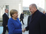 Turkey's President Recep Tayyip Erdogan right, welcomes Germany's Chancellor Angela Merkel, left, prior to the opening ceremony of a Turkish-German university's new campus, in Istanbul, Friday, Jan. 24, 2020. Merkel is meeting Turkish President Recep Tayyip Erdogan in Istanbul on Friday for talks that are expected to focus on the future of a migration deal between Turkey and the EU that helped decrease refugee flows to Europe. (Presidential Press Service via AP, Pool)