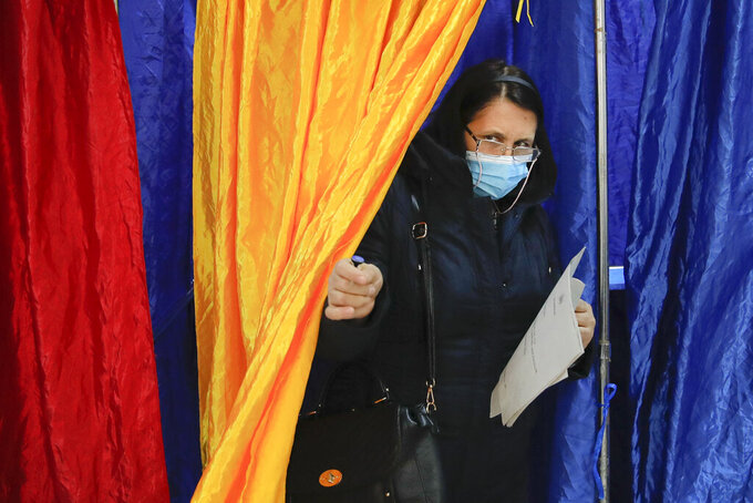 A woman wearing a mask for protection against the COVID-19 infection exits a voting cabin in Bucharest, Romania, Sunday, Dec. 6, 2020. Voting started in Romania's legislative election expected to restore some measure of stability after five years of political and social turbulence with more than 18 million Romanians registered to vote for a new legislative body. (AP Photo/Vadim Ghirda)