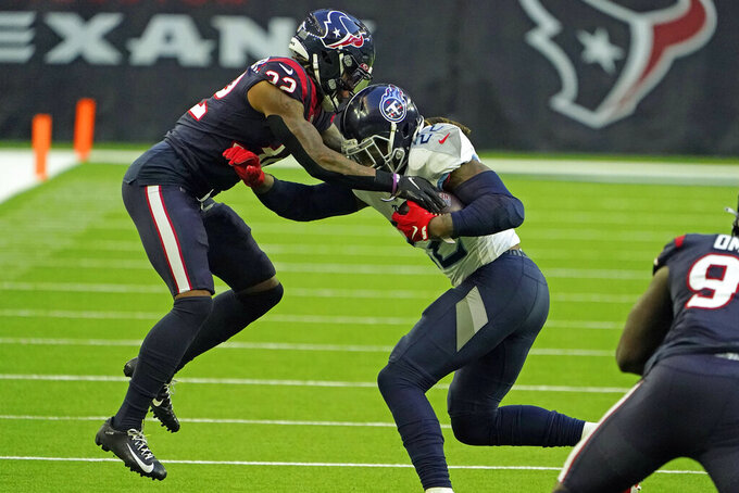 Tennessee Titans running back Derrick Henry (22) is tackled by Houston Texans cornerback Lonnie Johnson Jr. (32) during the second half of an NFL football game Sunday, Jan. 3, 2021, in Houston. (AP Photo/Eric Christian Smith)