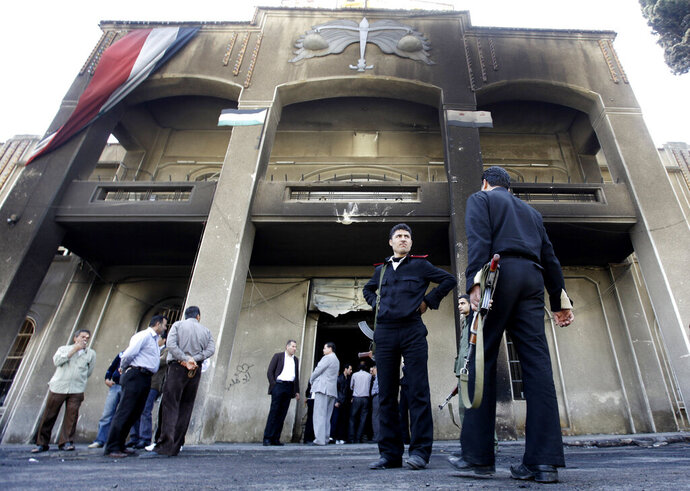 FILE - In this March 21, 2011 file photo, Syrian policemen stand in front of a court building that was set on fire by Syrian anti-government protesters, in the southern city of Daraa, Syria. The Syria Justice and Accountability Center, a Washington-based Syrian rights group said in a report, released Tuesday, May 21, 2019, that thousands of documents collected from abandoned Syrian government offices reveal the reach of President Bashar Assad's security agencies, offering a rare glimpse into the inner workings of his secretive apparatus. The documents include handwritten notes from top commanders to