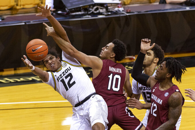 Missouri's Dru Smith, left, works against South Carolina's Justin Minaya (10) for a rebound during the first half of an NCAA college basketball game Tuesday, Jan. 19, 2021, in Columbia, Mo. (AP Photo/L.G. Patterson)