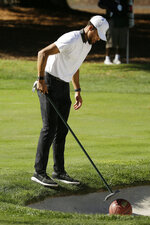 Stephen Curry uses a rake to retrieve a basketball from a bunker below the 17th green of the Silverado Resort North Course during the pro-am event of the Safeway Open PGA golf tournament Wednesday, Sept. 25, 2019, in Napa, Calif. (AP Photo/Eric Risberg)
