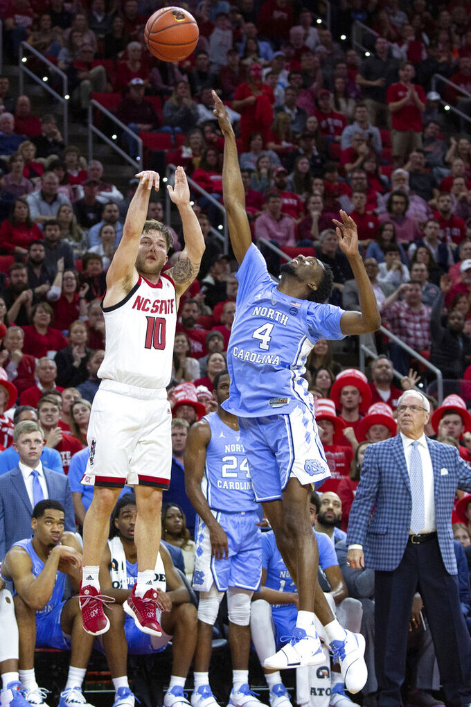 FILE - In this Jan. 8, 2019, file photo, North Carolina State's Braxton Beverly (10) attempts a three-pointer over North Carolina's Brandon Robinson (4) during the first half of an NCAA college basketball game, in Raleigh, N.C. N.C. State needs Beverly for his 3-point shooting ability. (AP Photo/Ben McKeown, File)