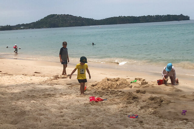 In this March 26, 2020, photo, tourists play on a beach in Phuket, Thailand. Tourists across Asia are finding their dream vacations have turned into travel nightmares as airlines cancel flights and countries close their borders in the fight against the coronavirus pandemic. (AP Photo/Penny Wang)
