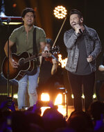 FILE - In this June 6, 2018 file photo, Dan Smyers, left, and Shay Mooney of musical group Dan + Shay, perform