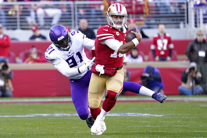 San Francisco 49ers quarterback Jimmy Garoppolo, right, runs from Minnesota Vikings defensive end Stephen Weatherly (91) during the first half of an NFL divisional playoff football game, Saturday, Jan. 11, 2020, in Santa Clara, Calif. (AP Photo/Tony Avelar)