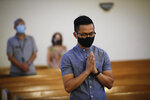 A man prays while wearing a face mask amid the coronavirus pandemic during a service at the San Gabriel Mission Sunday, July 12, 2020, in San Gabriel, Calif. A fire on Saturday destroyed the rooftop and most of the interior of the nearly 250-year-old California church that was undergoing renovation. (AP Photo/Marcio Jose Sanchez)