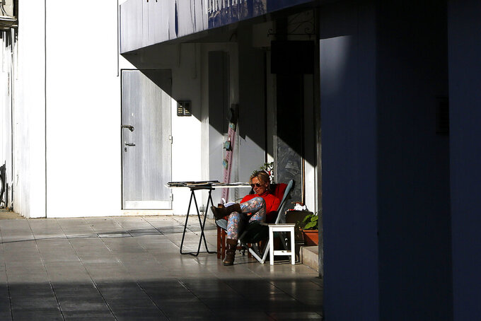 A woman sits in the sun and reads a book outside a shop in central capital Nicosia, Cyprus, Friday, March 12, 2021. Cyprus put the breaks on a wider loosening of COVID-19 restrictions by keeping middle school students at home for two more weeks as the infection rate remains high partly because of how widespread the U.K. variant has become. (AP Photo/Petros Karadjias)