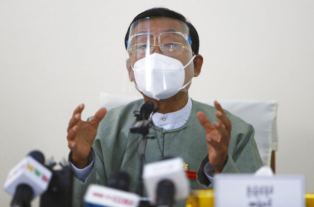 Myint Naing, a member of the Union Election Commission, wearing a protective face mask and shield, gestures as he delivers a speech during an event to announce election results Wednesday, Nov. 11, 2020, in Naypyitaw, Myanmar. The military backed main opposition party on Wednesday said it does not recognize last Sunday's Myanmar election, citing unfairness, and rejected the results. (AP Photo/Aung Shine Oo)