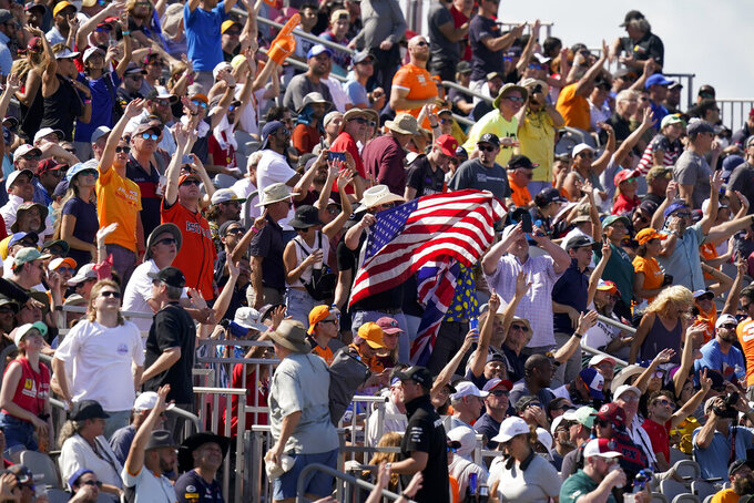 Spectators cheer at the start of the Formula One U.S. Grand Prix auto race at the Circuit of the Americas, Sunday, Oct. 24, 2021, in Austin, Texas. (AP Photo/Eric Gay)