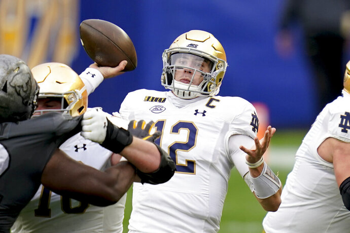 Notre Dame quarterback Ian Book (12) passes against Pittsburgh during the first half of an NCAA college football game, Saturday, Oct. 24, 2020, in Pittsburgh.  (AP Photo/Keith Srakocic)