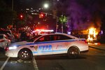 Police officers block off DeKalb Avenue in the Brooklyn borough of New York as a police vehicle burns after protesters gathered at Barclays Center to protest the death of George Floyd, a black man who died Memorial Day in Minneapolis police custody, Friday, May 29, 2020. (AP Photo/Frank Franklin II)