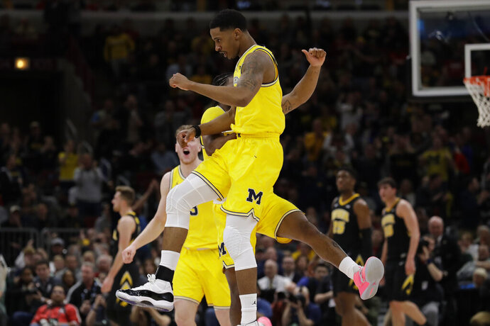 Michigan's Charles Matthews, front, celebrates with Zavier Simpson after scoring a 3-point basket during the first half of an NCAA college basketball game against the Iowa in the quarterfinals of the Big Ten Conference tournament, Friday, March 15, 2019, in Chicago. (AP Photo/Nam Y. Huh)