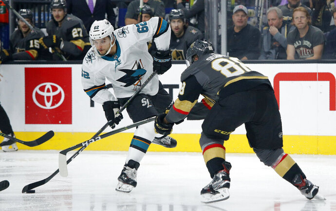San Jose Sharks right wing Kevin Labanc (62) attempts to skate around Vegas Golden Knights defenseman Nate Schmidt (88) during the first period of an NHL hockey game Thursday, Nov. 21, 2019, in Las Vegas. (AP Photo/John Locher)