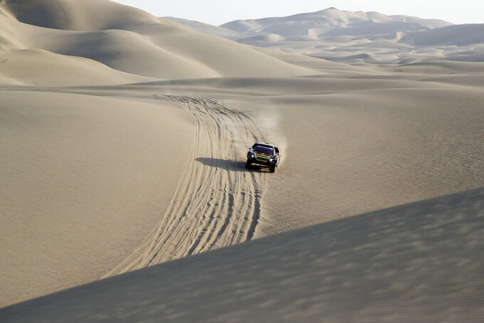 Driver Sebastien Loeb, of France, and co-driver Daniel Elena, of Monaco, race their Peugeot during the second stage of the Dakar Rally between Pisco and San Juan de Marcona, Peru, Tuesday, Jan. 8, 2019. (AP Photo/Ricardo Mazalan)
