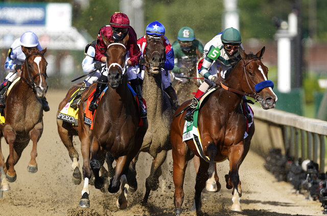 Florent Geroux rides Shedaresthedevil, second left, and John Velazquez rides Gamine, right, going into the first turn during the 146th running of the Kentucky Oaks at Churchill Downs, Friday, Sept. 4, 2020, in Louisville, Ky. (AP Photo/Mark Humphrey)