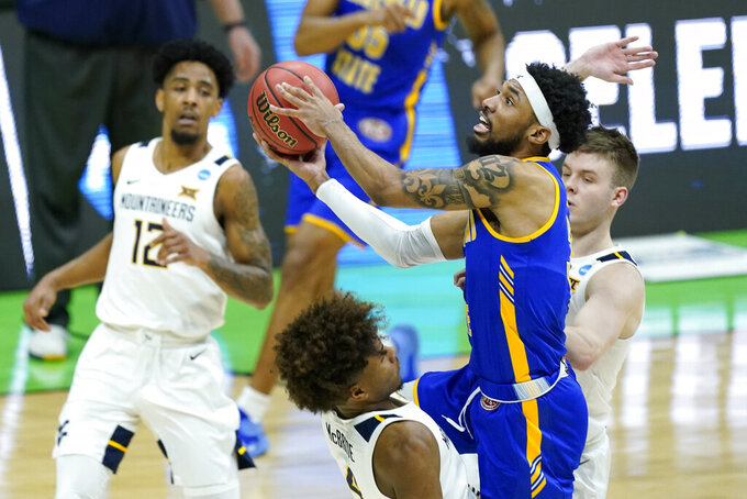 Morehead State's James Baker drives against West Virginia's Miles McBride (4) during the first half of a college basketball game in the first round of the NCAA tournament at Lucas Oil Stadium Friday, March 19, 2021, in Indianapolis. (AP Photo/Mark Humphrey)