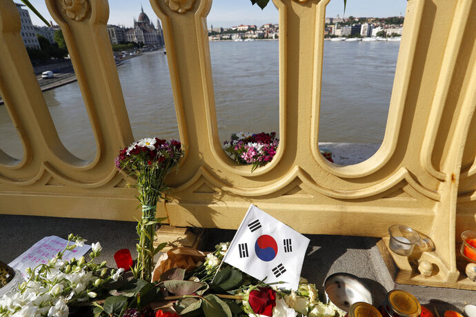 FILE - In this Saturday, June 1, 2019 file photo, flowers and flag of South Korea are laid on the Margit Bridge where a sightseeing boat capsized in Budapest, Hungary. Hungarian police say a South Korean woman recovered from the Danube River has been identified as the 27th fatality of the May 29 crash between a tour boat and a cruise ship. Police said Saturday, July 6 that the body was found some 58 kilometers (36 miles) downstream from the scene of the accident at Budapest's Margit Bridge. (AP Photo/Laszlo Balogh, file)