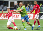 Seattle Sounders forward Jordan Morris (13) and New York Red Bulls midfielder Sean Davis (27) fight for possession Sunday, Sept. 15, 2019, in the second half of an MLS soccer match at CenturyLink Field in Seattle, Wash. (Joshua Bessex/The News Tribune via AP)