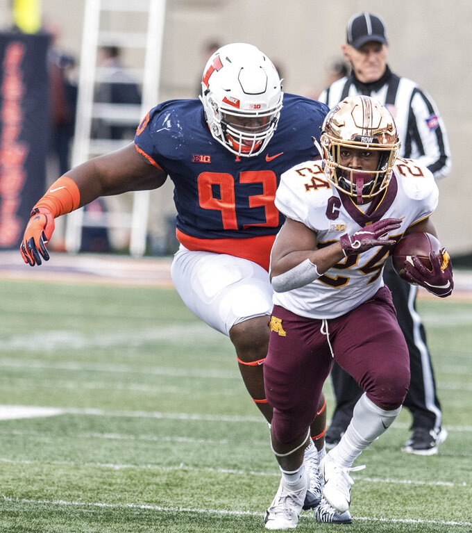 Minnesota's Mohamed Ibrahim (24) out runs the grasp of Illinois' Calvin Avery (93) in the first half of a NCAA college football game Saturday, Nov. 3, 2018, in Champaign, Ill. (AP Photo/Holly Hart)
