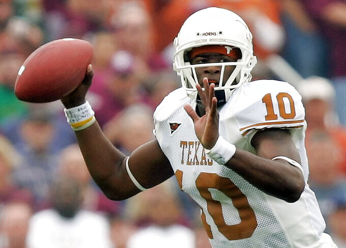 FILE - In this Nov. 25, 2005, file photo, Texas quarterback Vince Young looks to throw a pass against Texas A&M during the first quarter of an NCAA college football game in College Station, Texas. Texas has hired former Longhorns quarterback  Young as a special assistant in the athletic department, bringing the College Football Hall of Famer back to the program after he was fired in 2019. Young led the Longhorns to the 2005 season national championship with a last-minute touchdown against USC, before turning pro with an $25 million NFL contract. (AP Photo/David J. Phillip, File)