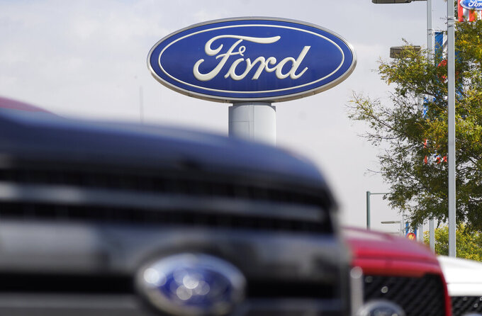 "FILE - In this Sunday, Oct. 11, 2020, file photo, the company logo hangs over a row of 2020 F-150 pickup trucks at a Ford dealership, in Denver. A global semiconductor shortage and a February 2021 winter storm have combined to force Ford to build F-150 pickup trucks without some computers. The company says the pickups will be held at factories for ""a number of weeks,"" then shipped to dealers once computers are available and quality checks are done. (AP Photo/David Zalubowski, File)"