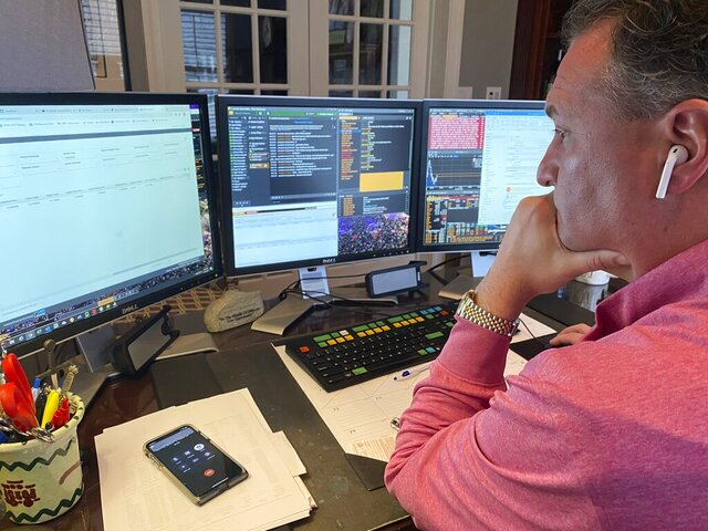 In this image provided by Jonathan Corpina, Jonathan Corpina, Senior Managing Partner at Meridian Equity Partners Inc., who normally works on the New York Stock Exchange trading floor, works in his home office in Armonk, NY., Wednesday, March 25, 2020. Stocks are wobbling in tentative trading Wednesday as a historic, worldwide rally downshifts dramatically after just a day. (Danielle Corpina/Courtesy Jonathan Corpina via AP)
