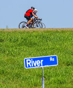Phil Baker, red shirt, a lifelong athlete who turns 80 on Aug. 28, begins his bicycle ride with his co-rider Britt Drummond Tuesday Aug. 24, 2021, in Baton Rouge, La. Baker is celebrating his 80th birthday by cycling 80 miles a day for 10 days straight.(Bill Feig/The Advocate via AP)
