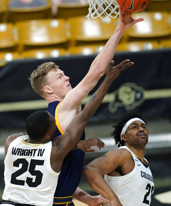 California forward Lars Thiemann, center, blocks a shot by Colorado guard McKinley Wright IV, front, as forward Evan Battey looks on in the second half of an NCAA college basketball game Thursday, Jan. 14, 2021, in Boulder, Colo. Colorado won 89-60. (AP Photo/David Zalubowski)