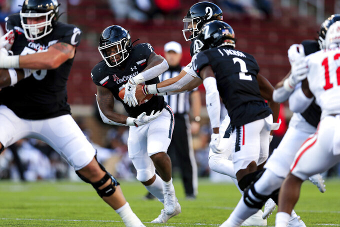 Cincinnati running back Gerrid Doaks, center, carries the ball during the first half of an NCAA college football game against Houston, Saturday, Nov. 7, 2020, in Cincinnati. (AP Photo/Aaron Doster)