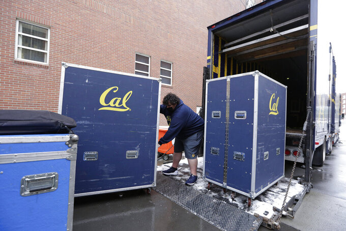 California equipment truck driver Dustin Sandoval loads equipment for his team into the trailer outside Martin Stadium after the NCAA college football game between Washington State and California was canceled due to COVID-19 positive testing and contact tracing on the California team, Saturday, Dec. 12, 2020, in Pullman, Wash. (AP Photo/Young Kwak)