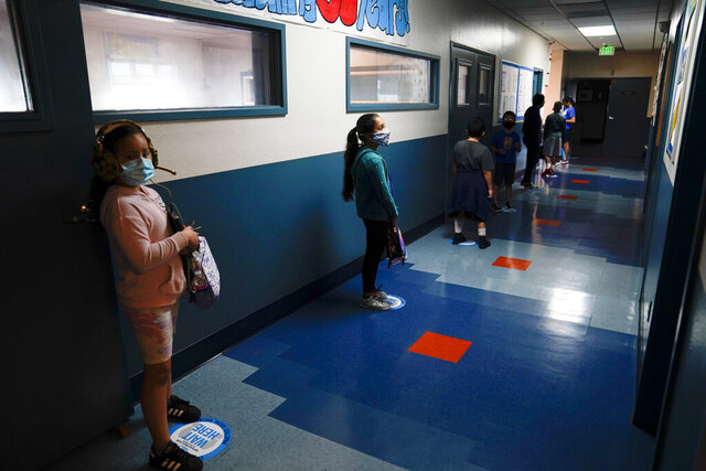 Los Angeles Unified School District students stand in a hallway socially distance during a lunch break at Boys & Girls Club of Hollywood in Los Angeles, Wednesday, Aug. 26, 2020. The LAUSD schools resumed classes with distance learning, but many underprivileged students still struggle, according to Mel Culpepper, CEO of Boys & Girls Club of Hollywood. The facility is open for children whose parents must leave home to work. There is no charge. Snacks and lunch are provided.