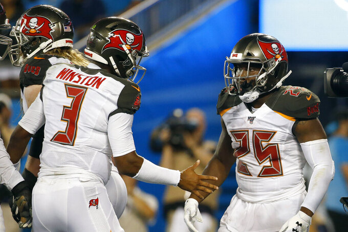 Tampa Bay Buccaneers quarterback Jameis Winston (3) congratulates running back Peyton Barber (25) following Barber's touchdown against the Carolina Panthers during the second half of an NFL football game in Charlotte, N.C., Thursday, Sept. 12, 2019. (AP Photo/Brian Blanco)