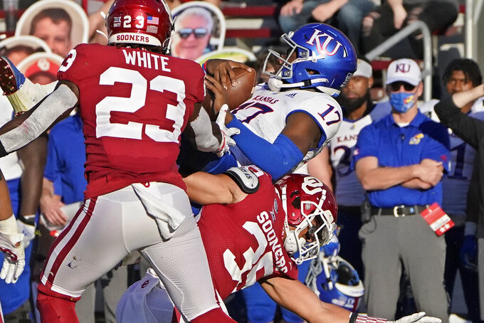 Kansas quarterback Jalon Daniels (17) is upended by Oklahoma linebacker Shane Whitter (35) in the first half of an NCAA college football game in Norman, Okla., Saturday, Nov. 7, 2020. (AP Photo/Sue Ogrocki)