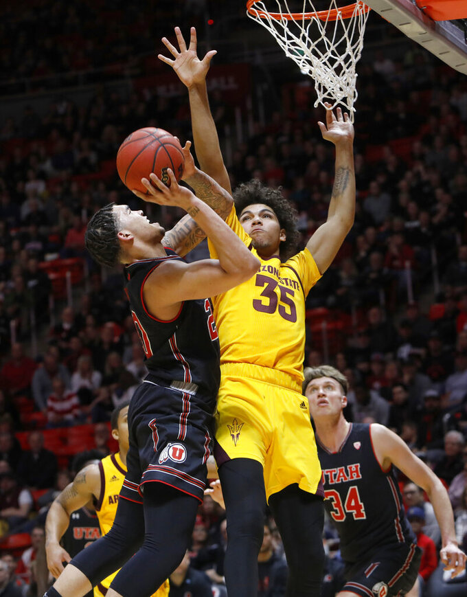 Utah's Timmy Allen, left, shoots as Arizona State's Taeshon Cherry (35) defends during the second half of an NCAA college basketball game Saturday, Feb. 16, 2019, in Salt Lake City. (AP Photo/Kim Raff)