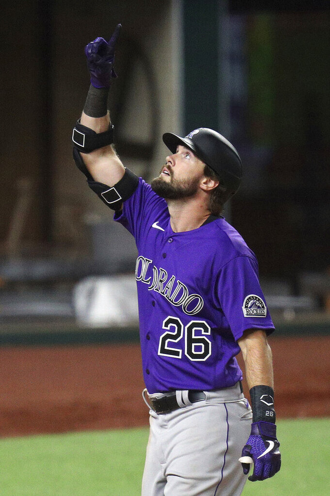 Colorado Rockies' David Dahl (26) gestures after scoring on his two-run home run in the fifth inning against the Texas Rangers in an exhibition baseball game, Tuesday, July 21, 2020 in Arlington, Texas. (AP Photo/Richard W. Rodriguez)