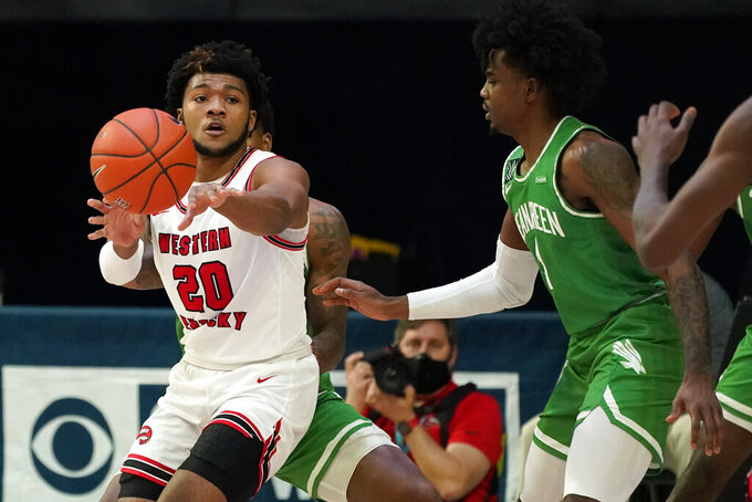 Western Kentucky guard Dayvion McKnight (20) passes around North Texas guard Mardrez McBride, right, during the first half of the championship game in the NCAA Conference USA men's basketball tournament Saturday, March 13, 2021, in Frisco, Texas. (AP Photo/Tony Gutierrez)