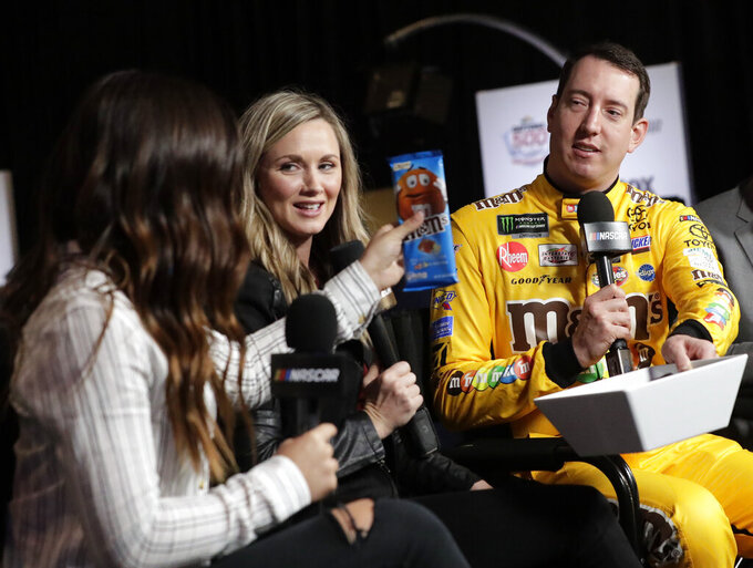 Kyle Busch, right, offers up candy provided by his sponsor to his hosts during an interview at NASCAR Daytona 500 auto racing media day at Daytona International Speedway, Wednesday, Feb. 13, 2019, in Daytona Beach, Fla. (AP Photo/John Raoux)