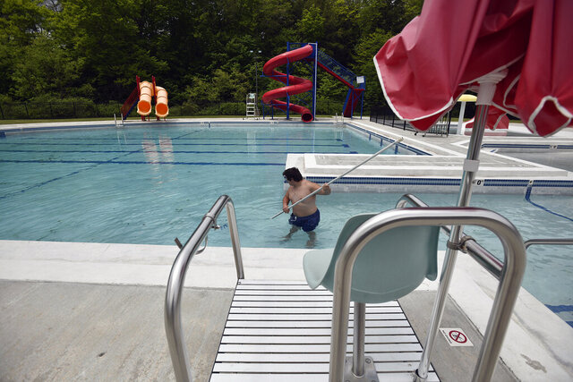 Ebensburg pool groundskeeper Zander Johnson scrubs the bottom of the pool getting it prepared for their June 13 opening with restrictions Thursday, June 4, 2020, in Ebensburg, Pa. (Todd Berkey/The Tribune-Democrat via AP)