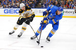 St. Louis Blues' Jay Bouwmeester (19) looks to clear the puck against Boston Bruins' Peter Cehlarik (22), of Slovakia, during the first period of an NHL hockey game Saturday, Feb. 23, 2019, in St. Louis. (AP Photo/Dilip Vishwanat)