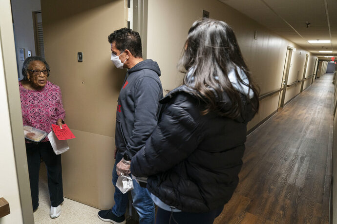Pearl Gailloux, 88, left, receives a Thanksgiving dinner and a holiday card from Meals on Wheels volunteers, Ted Fischer, center, and his daughter, Molly, 21, Wednesday, Nov. 25, 2020, at her home in Providence, R.I. As more at-risk seniors find themselves unable to leave their homes during the COVID pandemic, Meals on Wheels has been delivering on average 4,000 meals per day up from their pre-pandemic average of 1200. (AP Photo/David Goldman)