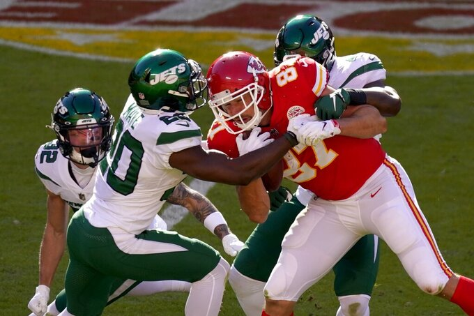 Kansas City Chiefs tight end Travis Kelce (87) is stopped after catching a pass by New York Jets' Ashtyn Davis (32), Marcus Maye (20) and others in the second half of an NFL football game on Sunday, Nov. 1, 2020, in Kansas City, Mo. (AP Photo/Charlie Riedel)