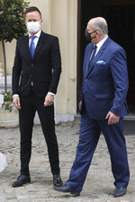 Poland's Foreign Minister Zbigniew Rau, right, walks with Hungarian Foreign Minister Peter Szijjarto during a meeting of foreign ministers from four central European countries known as the Visegrad Four in Lodz, Poland, Friday, May 14, 2021.(AP Photo/Czarek Sokolowski)