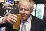 Britain's Prime Minister Boris Johnson tries some cider as he visits Healey's Cornish Cyder Farm during the General Election campaign, in Callestick, England, Wednesday, Nov. 27, 2019. Britain goes to the polls on Dec. 12. (Dan Kitwood/Pool Photo via AP)