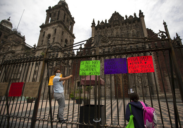 Newly graduated teachers from the state of Michoacan, hang signs on the fence of the city's cathedral, as they protest against Mexico's President Andres Manuel Lopez Obrador, demanding better salaries and jobs, in Mexico City, Thursday, Aug. 13, 2020. With the country facing a deep economic recession, Mexican President Andres Manuel Lopez Obrador has pushed to reopen the economy quickly even as COVID-19 infections and deaths continue to rise. (AP Photo/Fernando Llano)