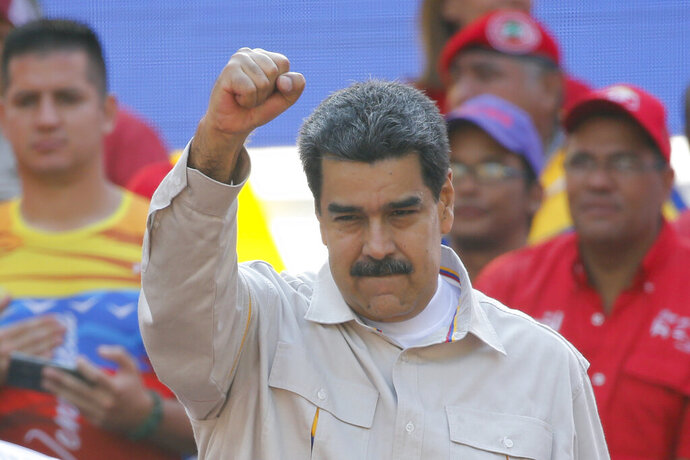 FILE - In this April 6, 2019 file photo, Venezuela's President Nicolas Maduro raises his fist to supporters rallying at the presidential palace in Caracas, Venezuela. The Associated Press has learned on Saturday, June 15, 2019, that major European nations are considering imposing sanctions on Maduro and several top officials for their recent crackdown on political opponents. (AP Photo/Ariana Cubillos, File)