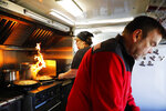 Sabine Cool, background, cooks potatoes as her husband, Jeff, prepares for a lunch crowd outside their German-style food truck that operates in the heart of a NASA complex in Huntsville, Ala., Wednesday, Jan. 9, 2019. The couple say they normally do between $800-$1,000 per day, but since the partial government shutdown began, they're averaging $300-$400. (AP Photo/David Goldman)